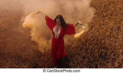 Aerial drone view of beautiful young woman in red transparent dress dancing with coloured smoke in rice field - colored video in slow motion