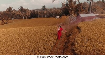 Beautiful woman with colored smoke in rice fields