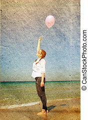 beautiful woman with colorful balloons outside. Photo in old image style.