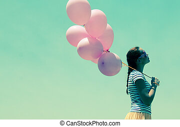 beautiful woman with colorful balloons outside