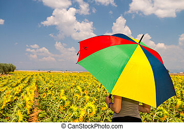 Beautiful woman with colorful umbrella on a Sunflowers field
