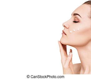 Beautiful woman with cream drops on cheek.