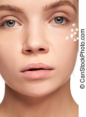 beautiful woman with cream face drops on her face