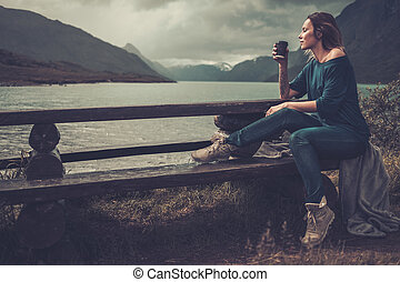 Beautiful woman with cup of coffee or tea sitting on a banch near the wild lake, with mountains on the background.