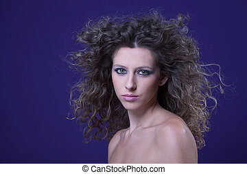 beautiful woman with curly hair on wind, on purple, studio shot