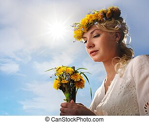 Beautiful woman with dandelion flowers over blue sky
