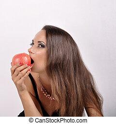 beautiful woman with dark hair eating an apple.