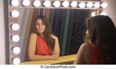 Beautiful woman with dark hair enjoying the way she looks in the mirror