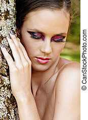beautiful woman with dramatic makeup and grey manicure.