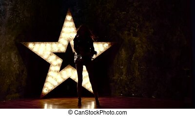 beautiful woman with electric guitar. sexy girl in leather, shining star in the background. slow motion, silhouette