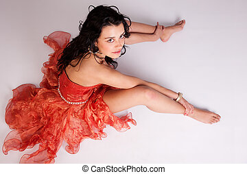 beautiful woman with elegant dress, on floor looking up, studio shot