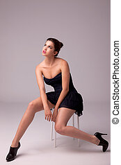 beautiful woman with elegant dress looking up to the light, sitting on a bench, studio shot.
