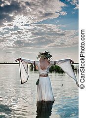 Attractive Woman with Wreath of Flowers walking in water of lake. Back view (Russian traditional holiday celebration)
