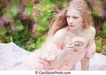 Beautiful woman with flowering tree drinking tea