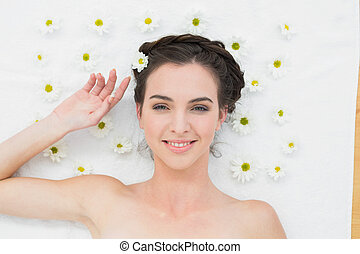 Overhead portrait of a beautiful young woman with flowers in beauty salon
