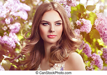 Beautiful woman with flowers of lilac