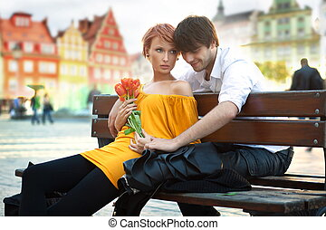 Beautiful woman with flowers on a date with handsome man