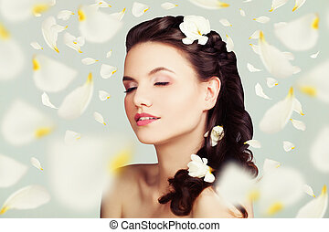 Beautiful Woman with Flowers Petals. Young Beauty. Brunette Fashion Model with Hairstyle and Makeup