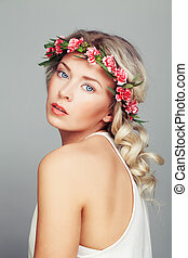 Beautiful Woman with Flowers Wreath. Blonde Curly Hair and Fashion Makeup