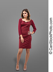 Beautiful woman with full lips in a burgundy dress over gray background in studio