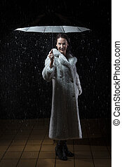 Beautiful woman with fur coat standing in rain under an umbrella at night