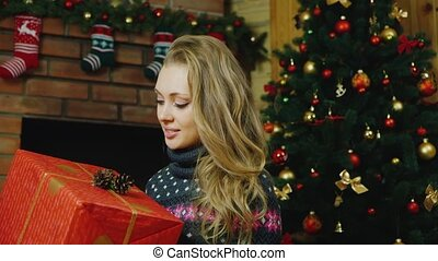 Beautiful woman with gifts around the Christmas tree