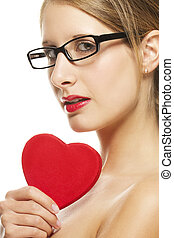 beautiful woman with glasses holding red heart on white background