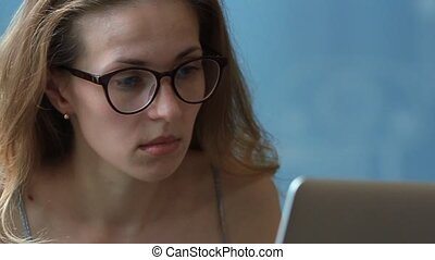 Beautiful woman with glasses using a laptop computer