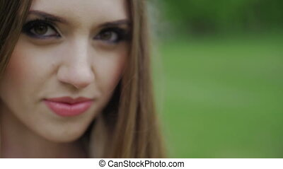 Beautiful woman with green eyes and brown hair looks on camera slow motion