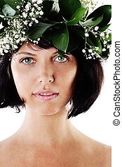 Beautiful Woman with Green Leaves and Flowers.