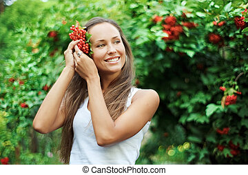 Beautiful woman with guelder rose in hair