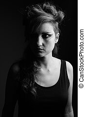 Studio shot of beautiful woman with hair tied and makeup against gray background in black and white