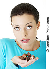 Beautiful woman with hand full of chocolates