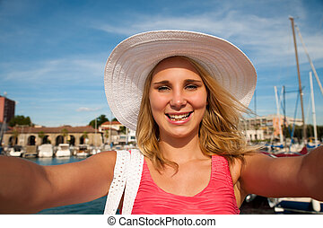 Beautiful woman with hat taking selfie on pier in a small costal city Koper Slovenia central Europe