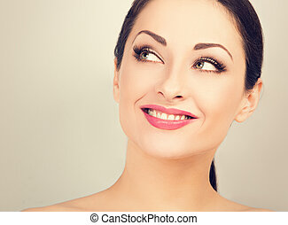 Beautiful woman with healthy clean face skin looking up and thinking with toothy smile. Correction eyebrows shape. Dental perfect health. Studio blue background. Closeup toned color portrait