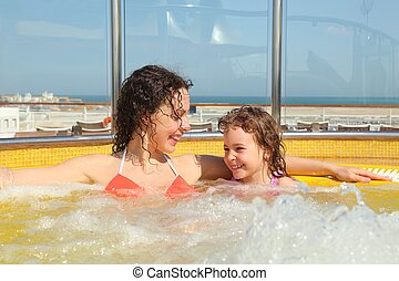 beautiful woman with her daughter both smiling in hot tub on...