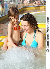 beautiful woman with her daughter in hot tub on cruise ship.