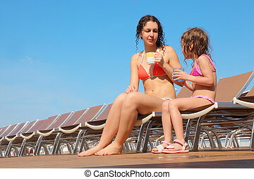 beautiful woman with her daughter sitting on chaise longues with mugs.