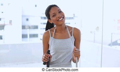 Beautiful woman with her jump rope in apartment