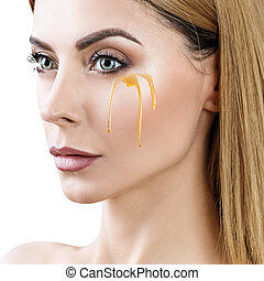 Beautiful woman with honey on face.