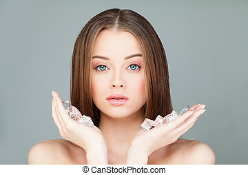 Beautiful Woman with Ice Cubes. Young Spa Model with Healthy Skin on Gray Background