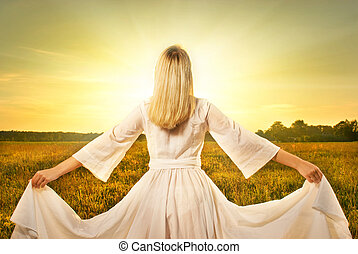 Beautiful woman with in the field at sunset