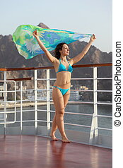 beautiful woman with kerchief is standing on deck of cruise ship.