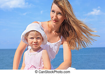 beautiful woman with little girl in white hat near sea