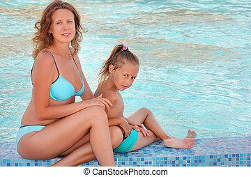 beautiful woman with little girl sit near in pool