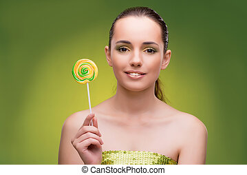 Beautiful woman with lollipop on green background