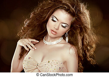 Beautiful woman with long brown curly hair and makeup. Hairstyle. Jewelry and Fashion.
