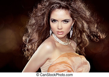Beautiful woman with long brown curly hair and makeup. Hairstyle. Jewelry. Jewellery.