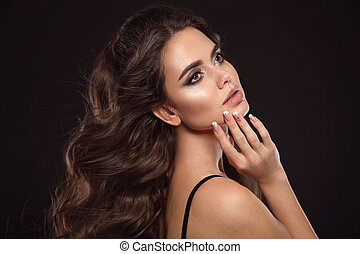Beautiful woman with long brown curly hair. Closeup portrait with a pretty face of the young girl. Fashion model with manicure nails posing isolated on black background at studio.