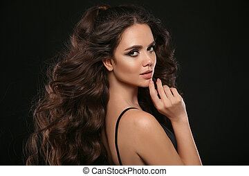 Beautiful woman with long brown curly hair. Closeup portrait with a pretty face of the young girl. Jewelry store copyscpace. Fashion model posing isolated on black background at studio.